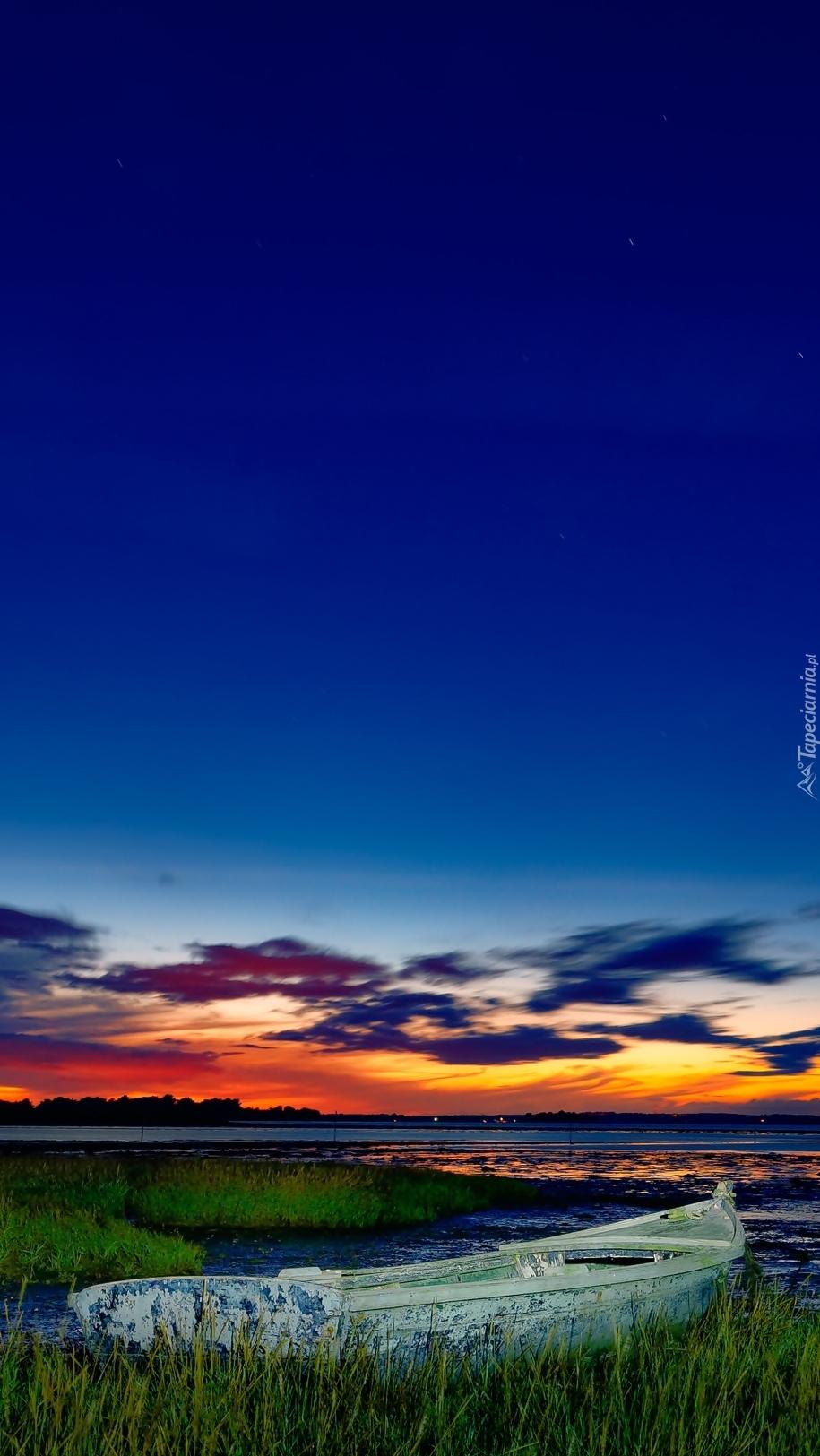 Zachód słońca nad jeziorem z łódką