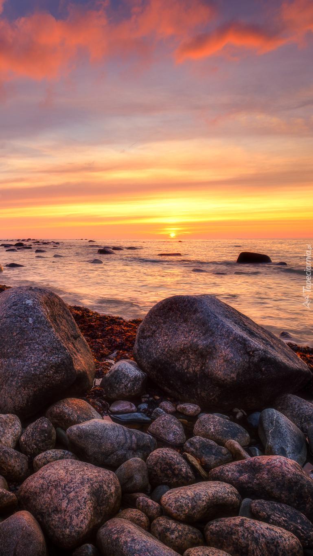 Zachód słońca nad kamienistym brzegiem morza