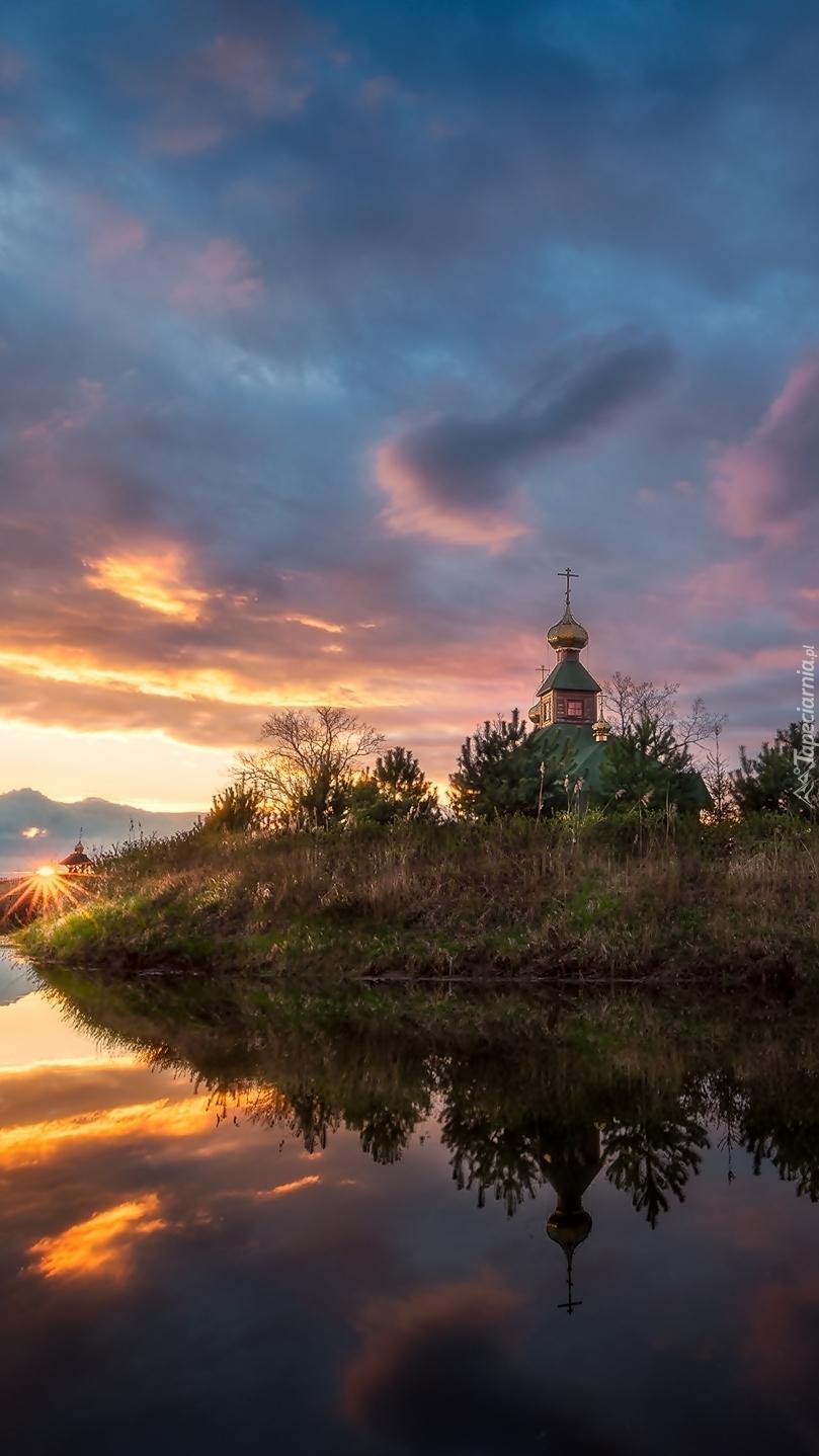 Zachód słońca nad kościołem i Narwią we wsi Ordynki