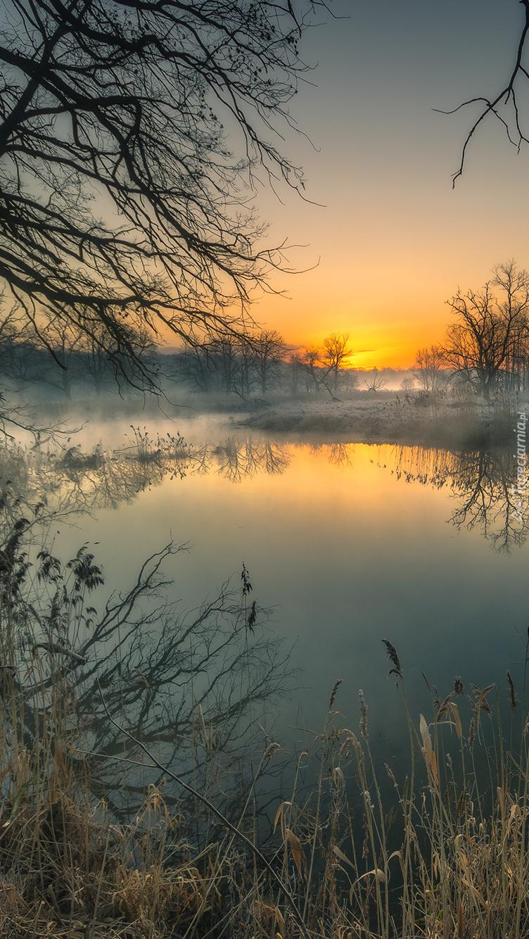 Zachód słońca nad zamglonym jeziorem