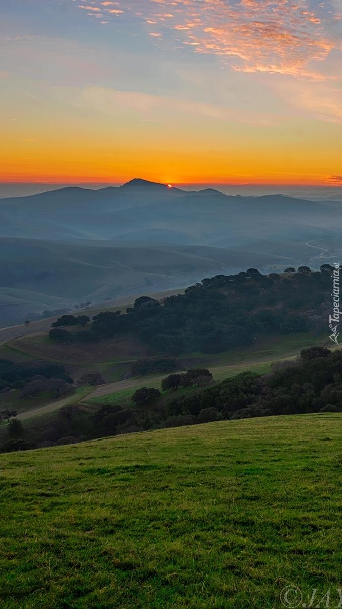 Zachód słońca nad zamglonymi wzgórzami