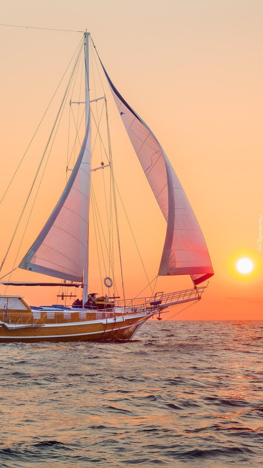 Żaglówka na morzu o wschodzie słońca