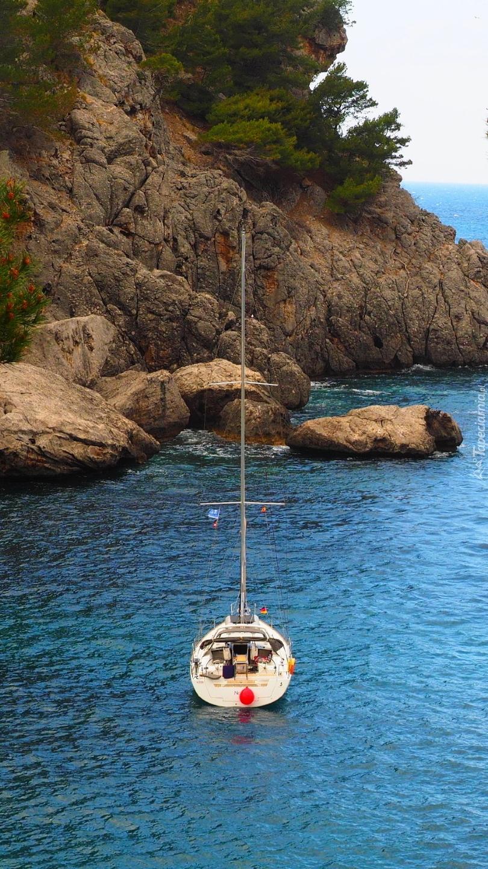 Żaglówka obok skał na brzegu morza
