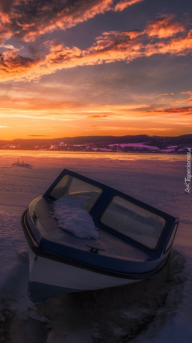 Zamarznieta motorówka na jeziorze zimą o zachodzie słońca.