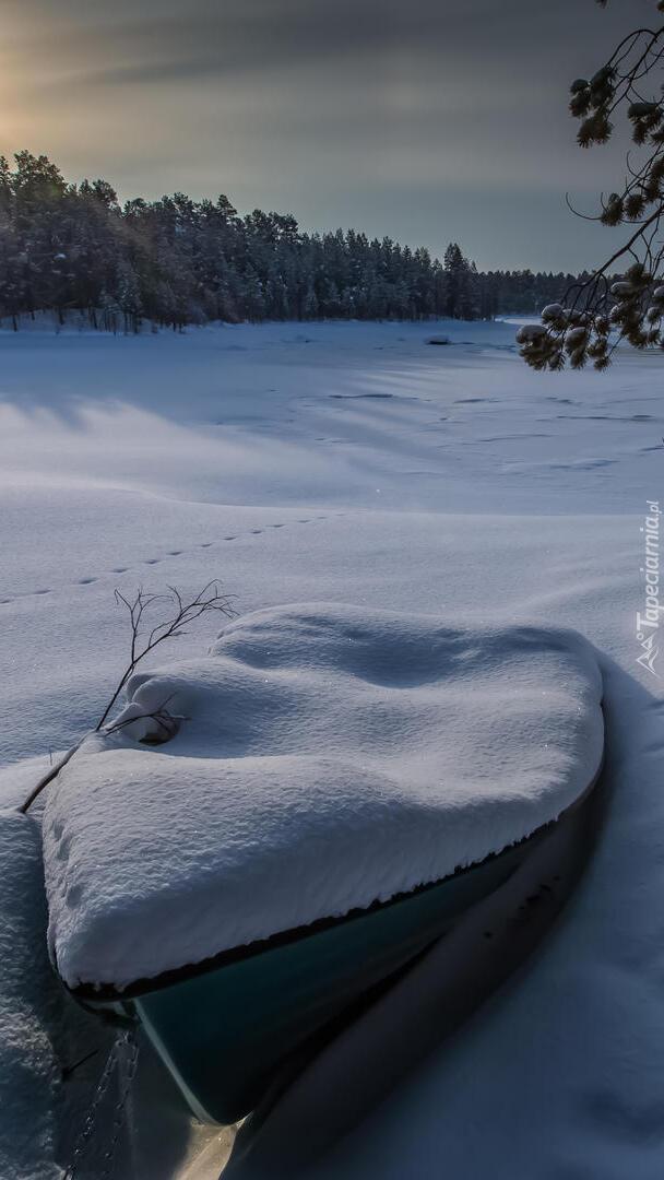 Zaśnieżona łódka i jezioro