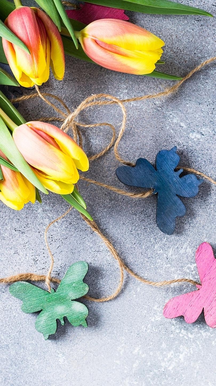 Zawieszki z motylami obok tulipanów
