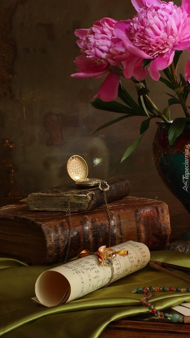 Zegarek na książkach obok piwonii