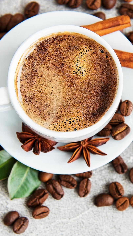 Ziarna kawy obok filiżanki