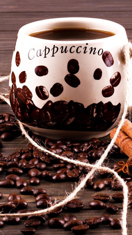 Ziarna kawy obok kubka z napisem cappuccino