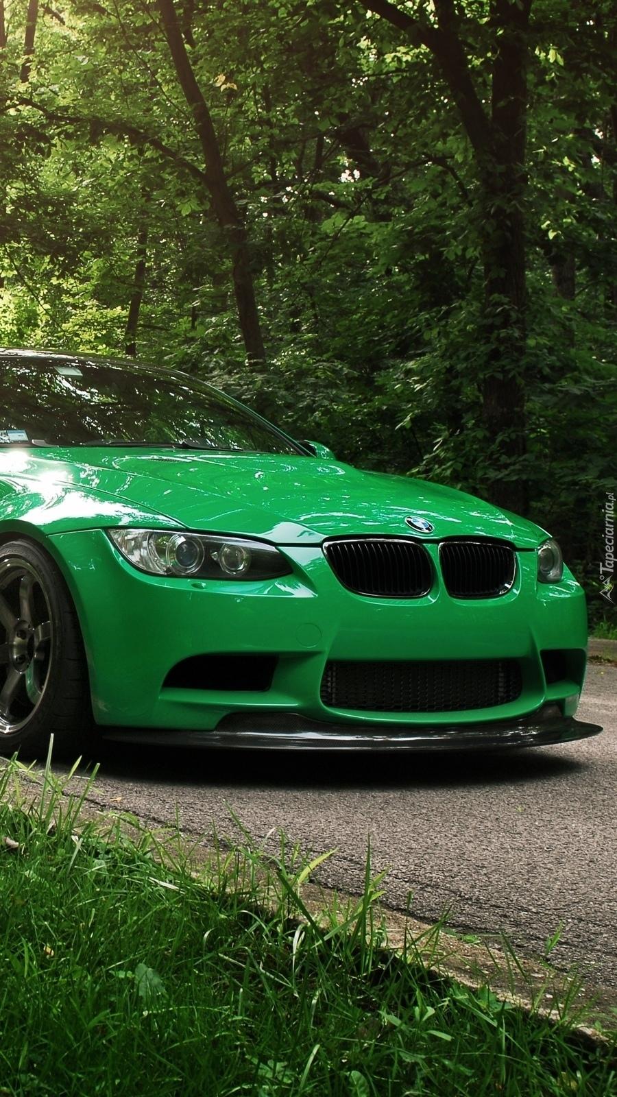 Zielone BMW na leśnej drodze