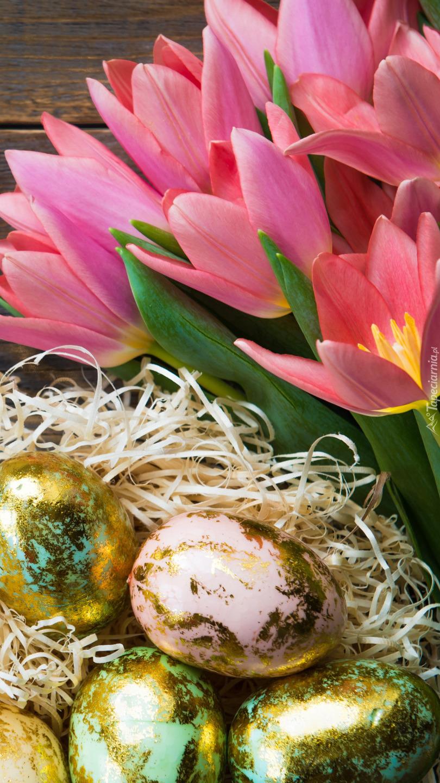 Złote jaja obok tulipanów