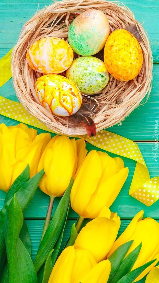Żółte tulipany obok gniazdka z pisankami