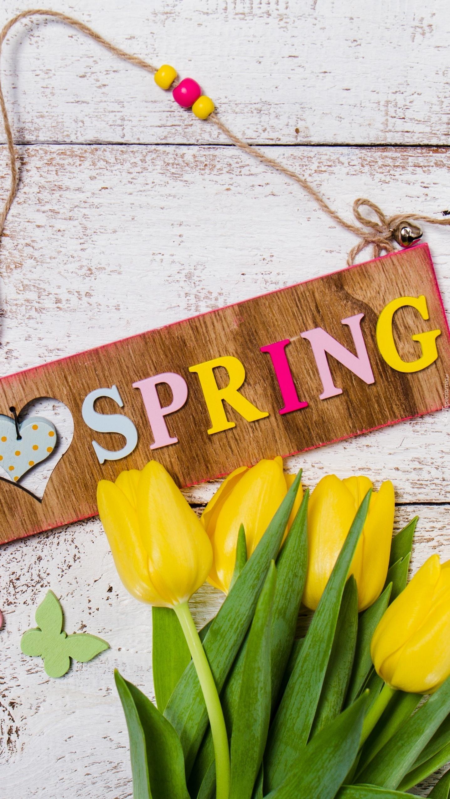 Żółte tulipany przy zawieszce z napisem Spring