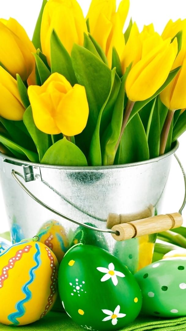 Żółte tulipany w wiaderku i pisanki wielkanocne