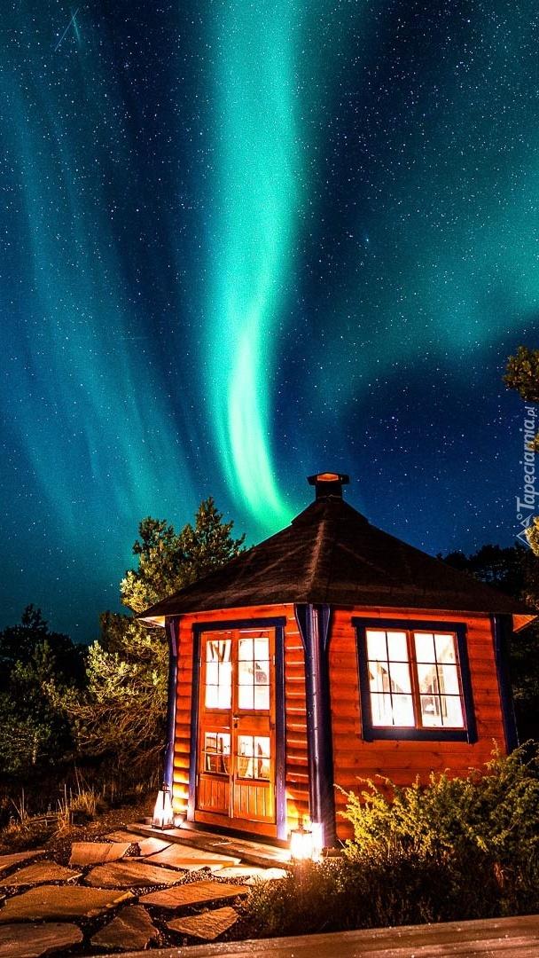 Zorza polarna nad oświetlonym domem