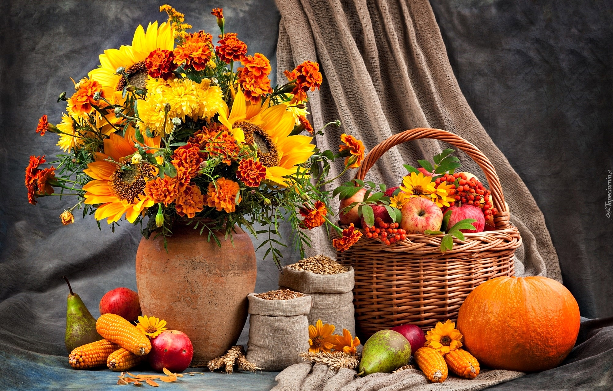 Bukiet jesiennych kwiatów obok koszyka z jabłkami i warzyw