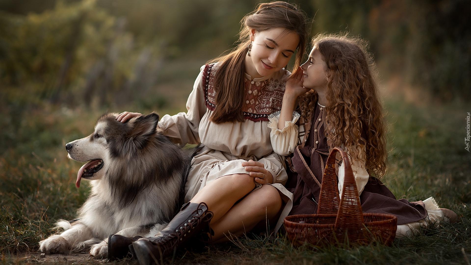 tapeta-dziewczynka-i-kobieta-siedzace-na-trawie-z-psem.jpg