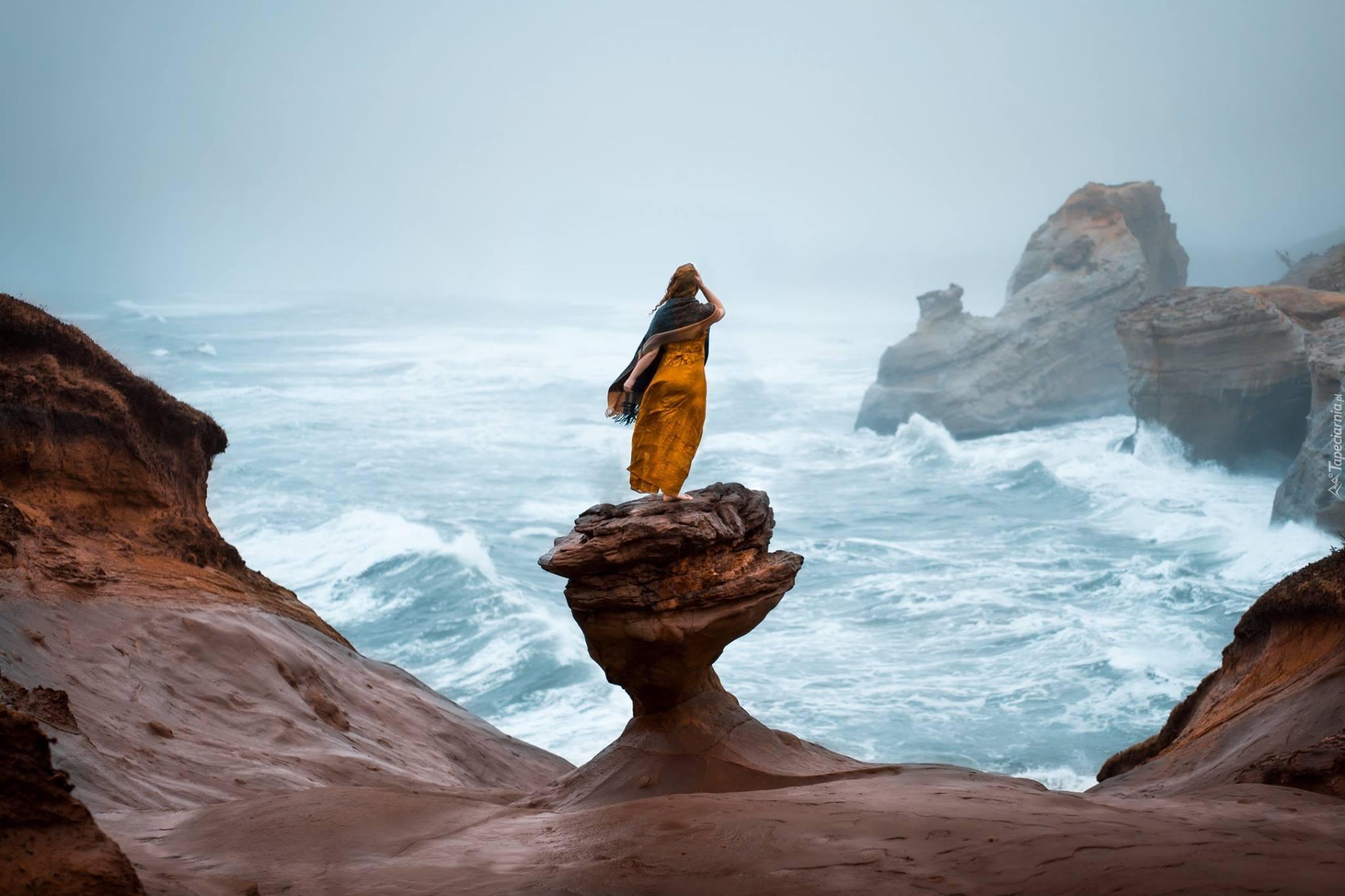 Kobieta na skale zapatrzona w morze